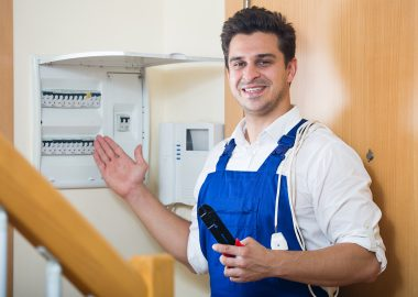Professional handyman near electric meter in domestic interior